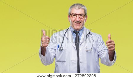 Handsome senior doctor man over isolated background success sign doing positive gesture with hand, thumbs up smiling and happy. Looking at the camera with cheerful expression, winner gesture.