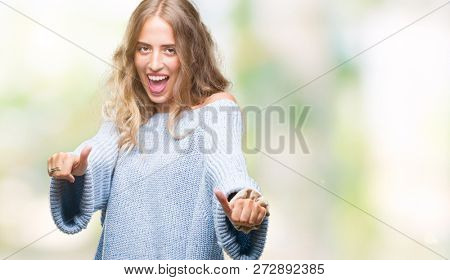 Beautiful young blonde woman wearing winter sweater over isolated background approving doing positive gesture with hand, thumbs up smiling and happy for success. Looking at the camera, winner gesture.