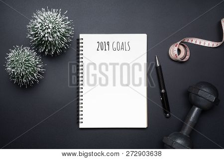 2019 New Years Resolutions Sport Flat Lay Composition. Black Dumbbells, Measurement Tape, Blank Note