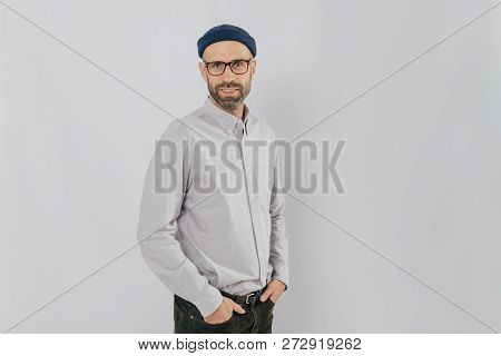 Sideways Shot Of Handsome Pleased Man Wears Stylish Hat, Keeps Hands In Pockets, Stands Against Whit