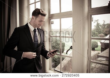 Handsome Business Executive Standing Next To Hotel Window Using His Mobile Cellphone Device