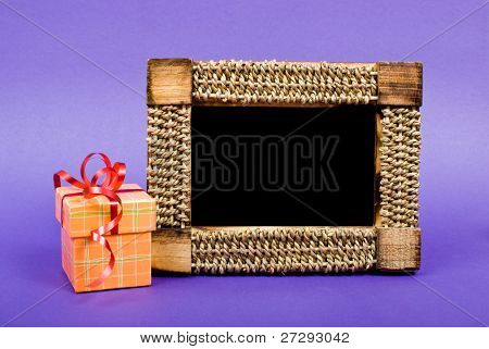 Wooden photo frame and orange gift box with red ribbon on blue background.