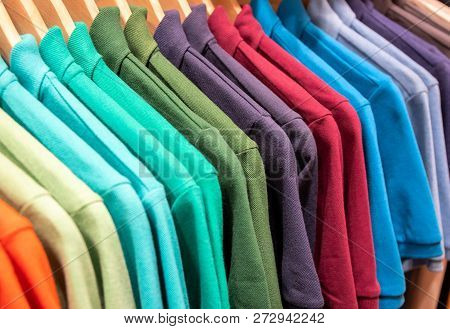 Vibrant Shirts On Hangs For Sale In Shop. Multicolored Polo On Wooden Hanger. Summer Fashion In Depa