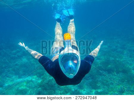Young Woman Diving Underwater Photo. Snorkel In Coral Reef Of Tropical Sea. Young Girl In Full-face