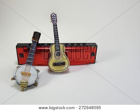 A Miniature Banjo And A Miniature Acoustic Guitar Propped Up On A Red 10-hole Diatonic Harmonica
