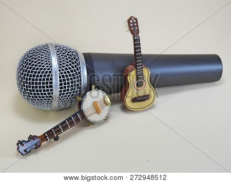 A Miniature Banjo And A Miniature Acoustic Guitar Propped Up On A Dynamic Handheld Vocal Microphone.