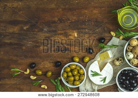 Set Of Cheese Camembert, Black And Green Olives, Quail Eggs On Plates, Olive Oil And Rosemary, Cashe