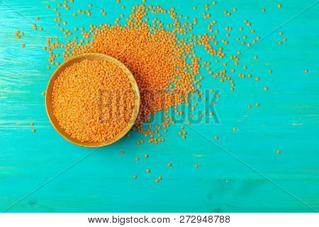 Red Lentils In Wood Plate On On A Blue Turquoise Wooden Table Background. Top View, Copy Space.