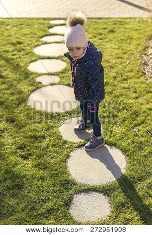 A Nice Little Girl With Blue Eyes In A Winter Suit And Stocking Cap Walks Along The Sidewalk. Concre