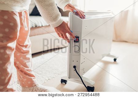 Using Heater At Home In Winter. Woman Turning Heater On. Heating Season.
