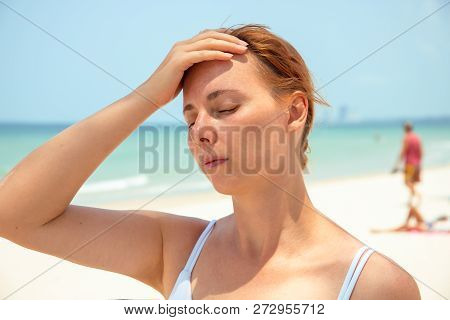 Sunstroke Woman On Sunny Beach. Woman With Headache. Hot Sun Danger. Health Problem On Holiday. Medi
