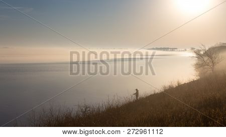 Silhouette Of A Fisherman On A Lakeshore On A Cold And Foggy Spring Morning Just After Sunrise.