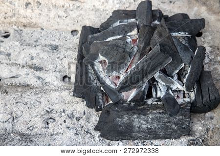 Black Coal With Flame Closeup Photo On Ash Background. Coal Pile Closeup Photo. Cooking Grill On Coa