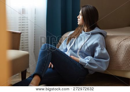 Indoor Shot Of Thoughtful Dark Haired Woman Dressed In Blue Sweatshirt, Jeans, Sits On Floor Near Be