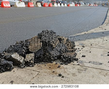 Pieces Of Fresh Asphalt On Sidewalk Near Repaired Carriageway. Image Can Be Used As Background.