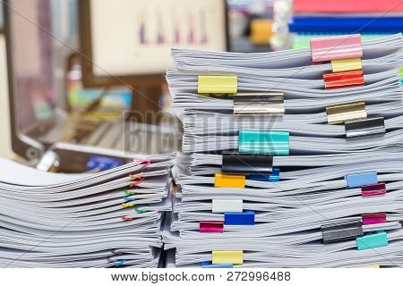 Pile Of Unfinished Documents On Office Desk. Stack Of Homework Assignment Archive With Colorful Clip