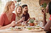 Four young adult friends eating in a restaurant, close up poster