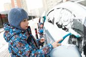 Portrait of child scraping snow from vehicle poster