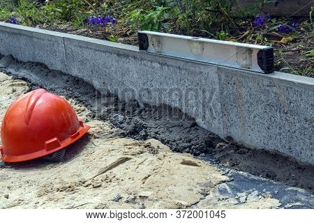 Installing Borders Before Laying Tiles Using A Bubble Level. Reconstruction Of The Sidewalk. Sidewal