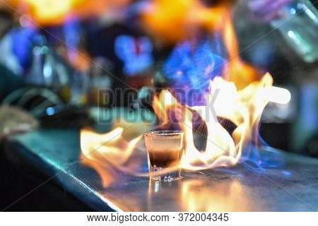 Glass With An Alcoholic Drink On Fire At A Bar Counter. Fiery Show At The Bar. The Bartender Makes H