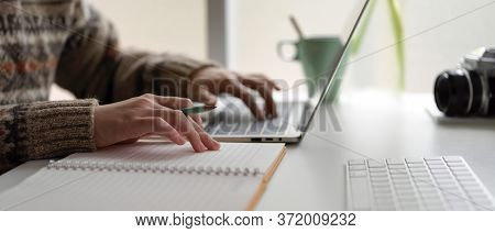 Female University Student Preparing Informations For Her Presentation With Laptop And Blank Notebook