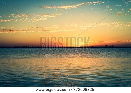 Shocking Sunset At The Edge Of The Lagoon. The Sun Sets On The Horizon Painting Everything In Golden
