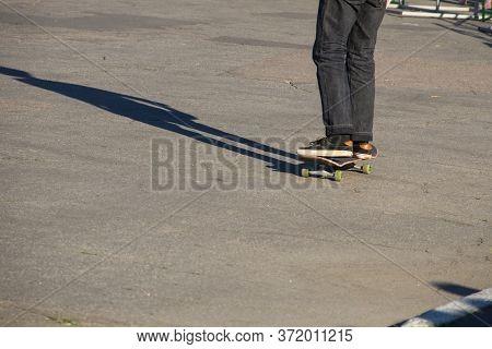 Skateboarder Legs Riding Skateboard At A Skatepark