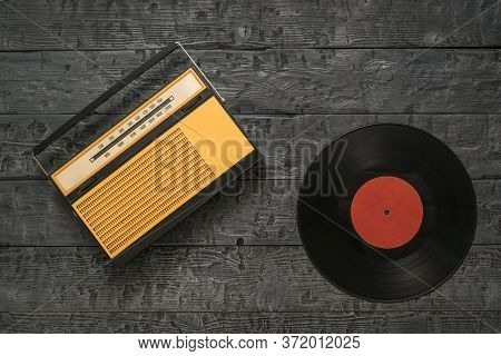 Retro Radio And Vinyl Disc On A Wooden Background. Radio Engineering Of The Past Time. The View From