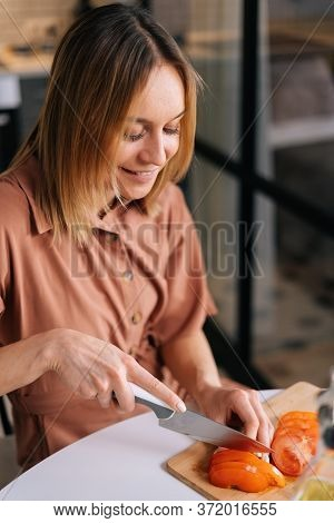 Portrait Of Young Woman Cutting Fresh Tomato Using Kitchen Knife On Wooden Cutting Board. Young Woma