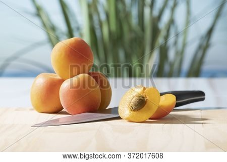 An Enticing Open Apricot With A Knife And A Small Pile Of Whole Apricots On A Cutting Board