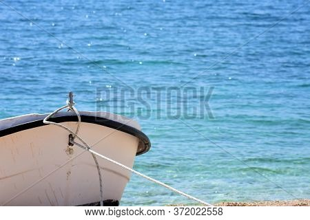 Tropical Seascape With A Wooden, Old And Broken White Boat On The Beach Whit Sea As Background