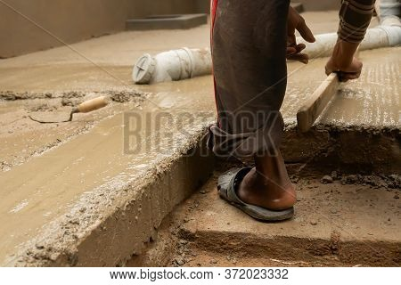 Indian Construction Worker Levelling A Cemented Floor Using Wooden Tool Manually, Stock Image.