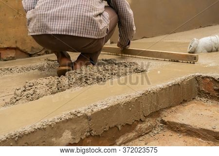Indian Construction Worker Levelling A Cemented Floor Using Wooden Leveller Manually, Stock Image.