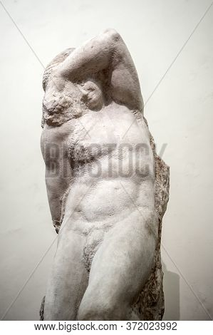Florence, Italy - October 2019: The Marble Statue Of Young Slave By Michelangelo Exhibited At The Ha