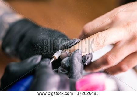 Close-up Of Manicurist Woman Removes Gel Shellac Polish From Clients Nails Using Manicure Machine. M