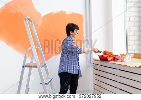 Renovation, Redecoration And Repair Concept - Middle-aged Woman Painting Wall In New Home.