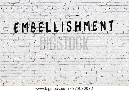 Word Embellishment Written With Black Paint On White Brick Wall.