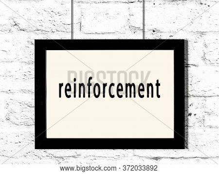Black Wooden Frame With Inscription Reinforcement Hanging On White Brick Wall