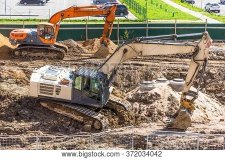 Two Excavators On Excavated Soil During The Construction Of A Road In The City