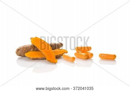 Nutrional Supplement Curcumin.tturmeric Root And Gel Capsules Isolated On White Background.