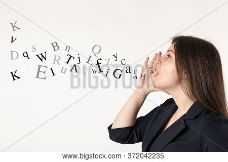 Young Woman In Blue Is Screaming At Something. Voice, Screaming And Letters Concept.