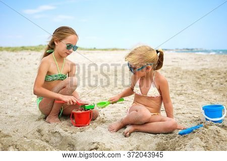Children Play With Sand On The Beach.