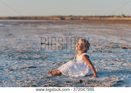 Little Happy Child Girl In A White Summer Dress Frolics Cheerfully On The Seashore In The Background