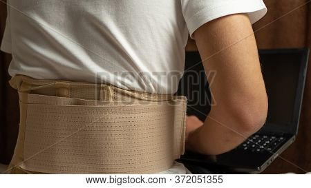 Man Wearing Orthopedic Corset At Home. Person With A Laptop Wearing In The Lumbosacral Brace Sitting