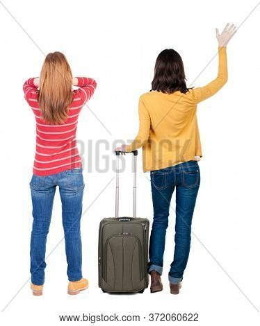Back view of two woman in sweater traveling with suitcas. Back view. Rear view people collection. backside view of person. Isolated over white background.