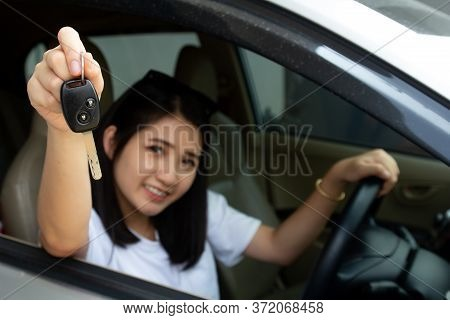 Asian Car Driver Woman Smiling Showing New Car Key. Happy Young Girl Owner Taking Car Key From Deale