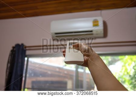 Woman Hand Holding Remote Control Directed To Air Conditioner Adjust Cold Temperature, Close Up. Wom