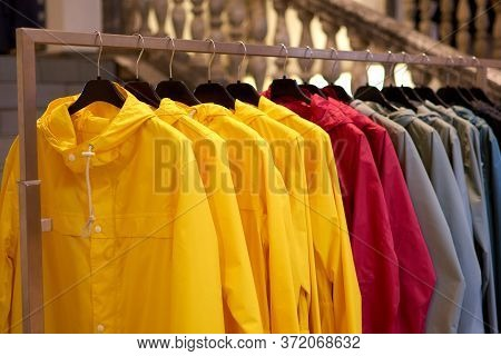 Bright Colorful Autumn Raincoats Hanging At A Fashion Store. Closeup Of Multi-colored Yellow, Red, G
