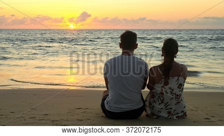 Silhouette Of Lovely Young Couple Sits On Empty Ocean Beach Watching Sunset At Tropical Resort In Ev