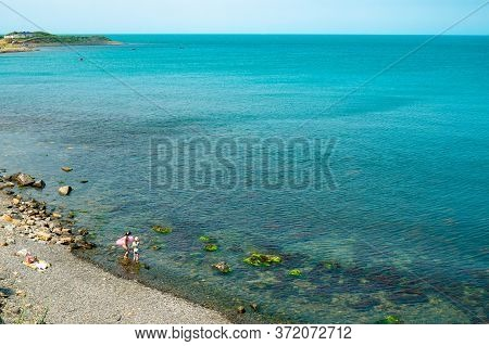 The Black Sea Coast With Resting Mom And Daughter On The Shore. Vacationing Family On The Beach With